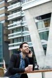 Junger Mann, der durch Handy nennt Stockbilder