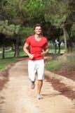 Junger Mann, der durch Park läuft Stockfoto