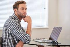 Junger Mann, der durchdacht den Abstand, seine Arbeit zögernd untersucht Stockbild