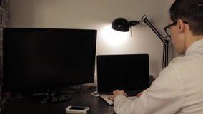 Junger Mann, der durchdacht schaut und Laptop verwendet stock video footage