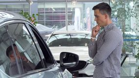Junger Mann, der durchdacht sein Kinn, Neuwagen beschließend, um an der Verkaufsstelle zu kaufen reibt stock footage