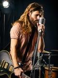 Junger Mann, der E-Gitarre auf Stadium singt und spielt Lizenzfreies Stockfoto