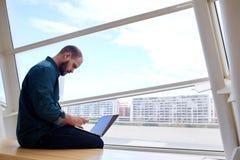 Junger Mann, der E-Mail am Handy während der Arbeit über Laptop-Computer beim Sitzen nahe großem Bürofenster überprüft Stockfoto