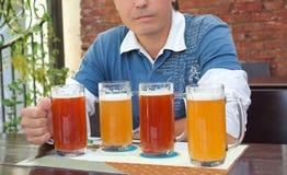 Junger Mann, der ein Bier an einem Stab genießt Stockfoto