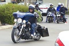 Junger Mann, der ein blaues Motorrad reitet Stockbild