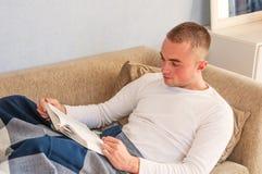 Junger Mann, der ein Buch liest Stockbild