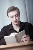 Junger Mann, der ein Buch liest Stockfotografie