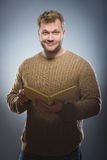 Junger Mann, der ein Buch liest und auf grauem Hintergrund lächelt Stockfotografie