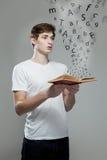 Junger Mann, der ein Buch mit Alphabetbuchstaben hält Stockfoto