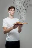 Junger Mann, der ein Buch mit Alphabetbuchstaben hält Stockfotografie