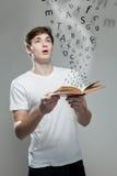 Junger Mann, der ein Buch mit Alphabetbuchstaben hält Stockbild