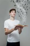 Junger Mann, der ein Buch mit Alphabetbuchstaben hält Lizenzfreie Stockfotos