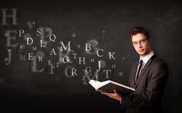 Junger Mann, der ein Buch mit Alphabetbuchstaben liest Lizenzfreies Stockbild