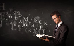 Junger Mann, der ein Buch mit Alphabetbuchstaben liest Stockfotografie