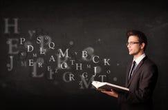Junger Mann, der ein Buch mit Alphabetbuchstaben liest Stockbild