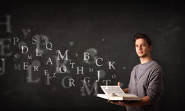 Junger Mann, der ein Buch mit Alphabetbuchstaben liest Lizenzfreie Stockbilder