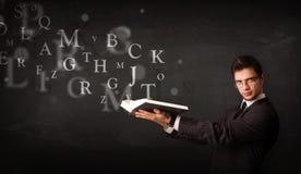 Junger Mann, der ein Buch mit Alphabetbuchstaben liest Lizenzfreie Stockfotografie