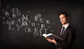 Junger Mann, der ein Buch mit Alphabetbuchstaben liest Lizenzfreies Stockfoto