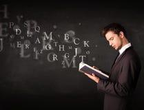 Junger Mann, der ein Buch mit Alphabetbuchstaben liest Lizenzfreie Stockfotos