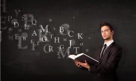 Junger Mann, der ein Buch mit Alphabetbuchstaben liest Stockbilder