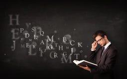 Junger Mann, der ein Buch mit Alphabetbuchstaben liest Stockfotos
