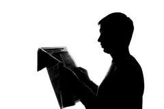 Junger Mann, der ein Buch - Schattenbild liest Stockfotos