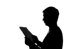 Junger Mann, der ein Buch - Schattenbild liest Stockbilder