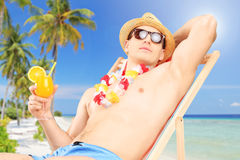 Junger Mann, der ein Cocktail hält und auf einem Sonnenruhesessel sitzt Stockfoto