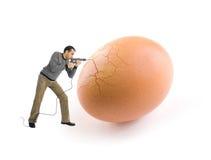Junger Mann, der ein Ei unter Verwendung eines Bohrgeräthilfsmittels knackt Lizenzfreie Stockfotos