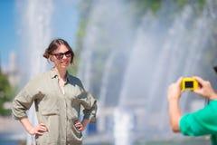 Junger Mann, der ein Foto seiner Freundin beim Sitzen des Hintergrundes der Brunnen macht Junger Mann, der an Foto von der Frau m Lizenzfreies Stockfoto