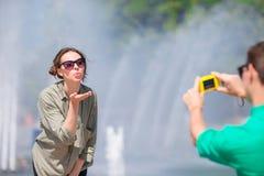 Junger Mann, der ein Foto seiner Freundin beim Sitzen des Hintergrundes der Brunnen macht Junger Mann, der an Foto von der Frau m Stockfotografie