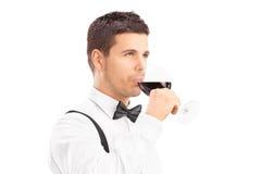 Junger Mann, der ein Glas Rotwein genießt Stockfotos