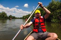 Junger Mann, der in ein Kanu reist lizenzfreies stockfoto