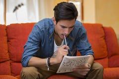 Junger Mann, der ein Kreuzworträtsel tuend sitzt Lizenzfreie Stockfotos