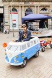 Junger Mann, der ein Miniatur-Volkswagen-Reisemobil fährt Stockbilder