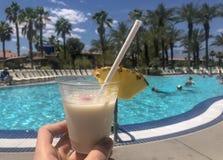 Junger Mann, der ein pina colada tropisches Getränk in seinen Händen am Pool im Sommer mit tropischen Palmen im Hintergrund hält stockfoto