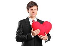 Junger Mann, der ein rotes Herz hält Stockbilder