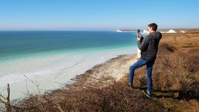 Junger Mann, der ein schönes seaview und eine cliffed Küstenlinie an der Aktionskamera filmt stock video footage