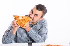 Junger Mann, der ein Stück vegetarische Pizza beißt Stockfoto