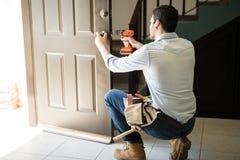 Junger Mann, der ein Türschloss repariert Lizenzfreie Stockfotos