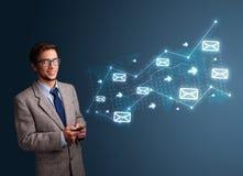 Junger Mann, der ein Telefon mit Pfeilen und Mitteilungsikonen hält Lizenzfreies Stockfoto