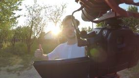 Junger Mann, der ein Video außerhalb seines Hauses mit einer beweglichen Berufskamera über sein Dorf in der Natur spinnt und noti stock video footage