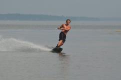 Junger Mann, der ein Wakeboard in Maine-` s Casco Bucht reitet stockfoto