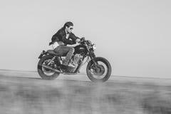 Junger Mann, der ein Weinlesemotorrad reitet Kameraschwenk für Bewegungsunschärfe Stockfotos