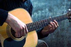 Junger Mann, der eine Akustikgitarre auf dem Hintergrund einer Betonmauer spielt Lizenzfreie Stockfotos