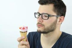 Junger Mann, der eine Eiscreme schaut Stockbild