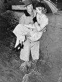 Junger Mann, der eine Frau durch einen Regensturm trägt (alle dargestellten Personen sind nicht längeres lebendes und kein Zustan Stockbild