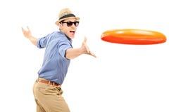 Junger Mann, der eine Frisbeescheibe wirft Lizenzfreies Stockfoto