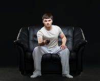Junger Mann, der eine Fußballsendung aufpasst Stockfoto