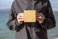 Junger Mann, der eine Geschenkbox in seinen Händen hält lizenzfreie stockbilder